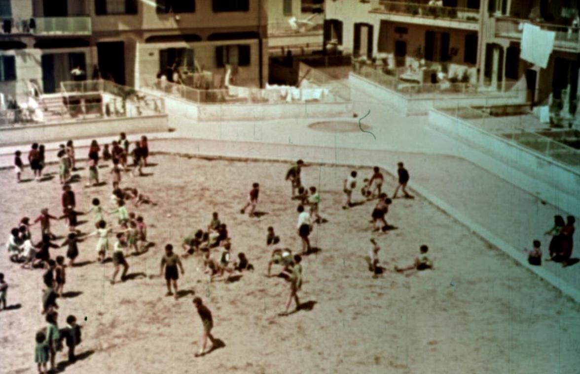 Frame di Case per il popolo con bambini che giocano nel nuovo quartiere Ina-Casa del Quadraro (1953)